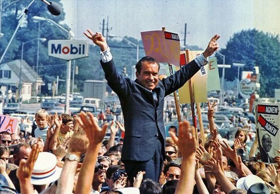 "Richard Nixon gives his trademark ""victory"" sign."
