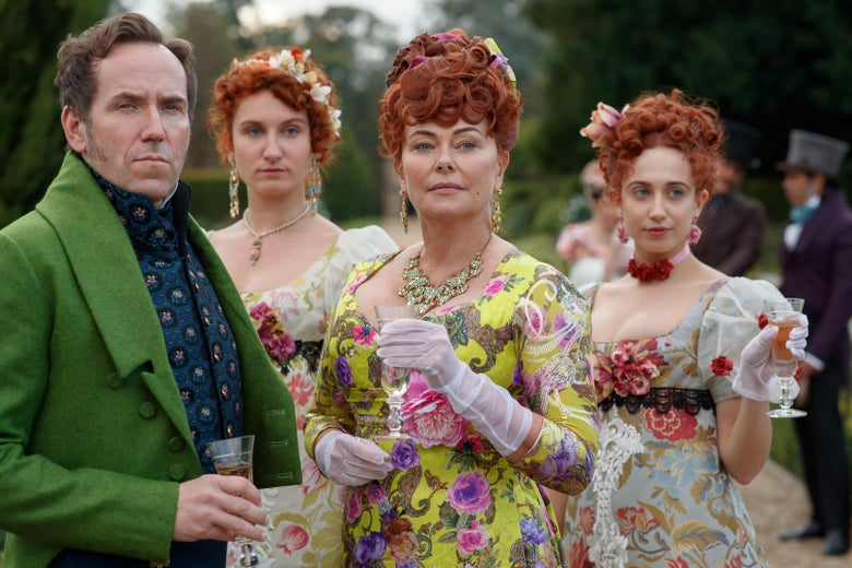 Ben Miller as Lord Featherington, wearing a bright green coat, stands with Polly Walker, who wears a yellow dress with a busy pattern of pink and purple flowers. Behind them, Harriet Cains as Philippa wears a low-cut floral dress with ruffled sleeves.