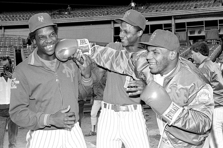 Mike Tyson shows Dwight Gooden how he does it by landing a long right to the amusement of Darryl Strawberry (center) at Shea Stadium prior to the game against the Expos on Sep. 9, 1986.