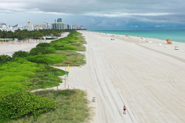 An aerial view of an empty beach, with the Miami skyline in the background.