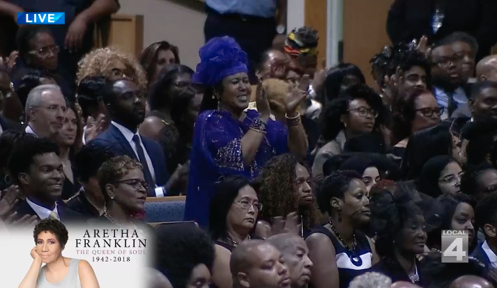 A woman in a purple ruffled hat and a purple jeweled top stands and claps in the audience of Aretha Franklin's funeral