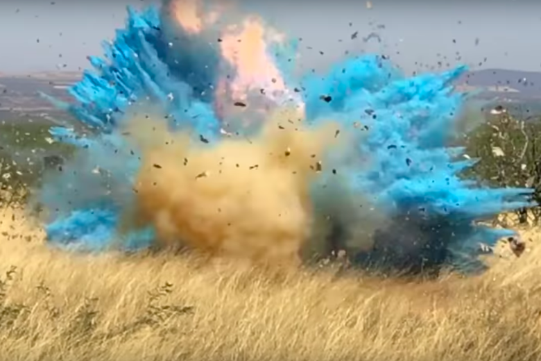 In a still from the video, a viewer can see an explosion of fire and blue in a grasslands setting.