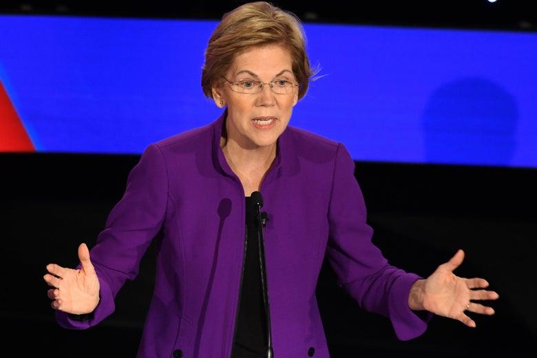 Elizabeth Warren, wearing a purple jacket, gestures as she speaks.