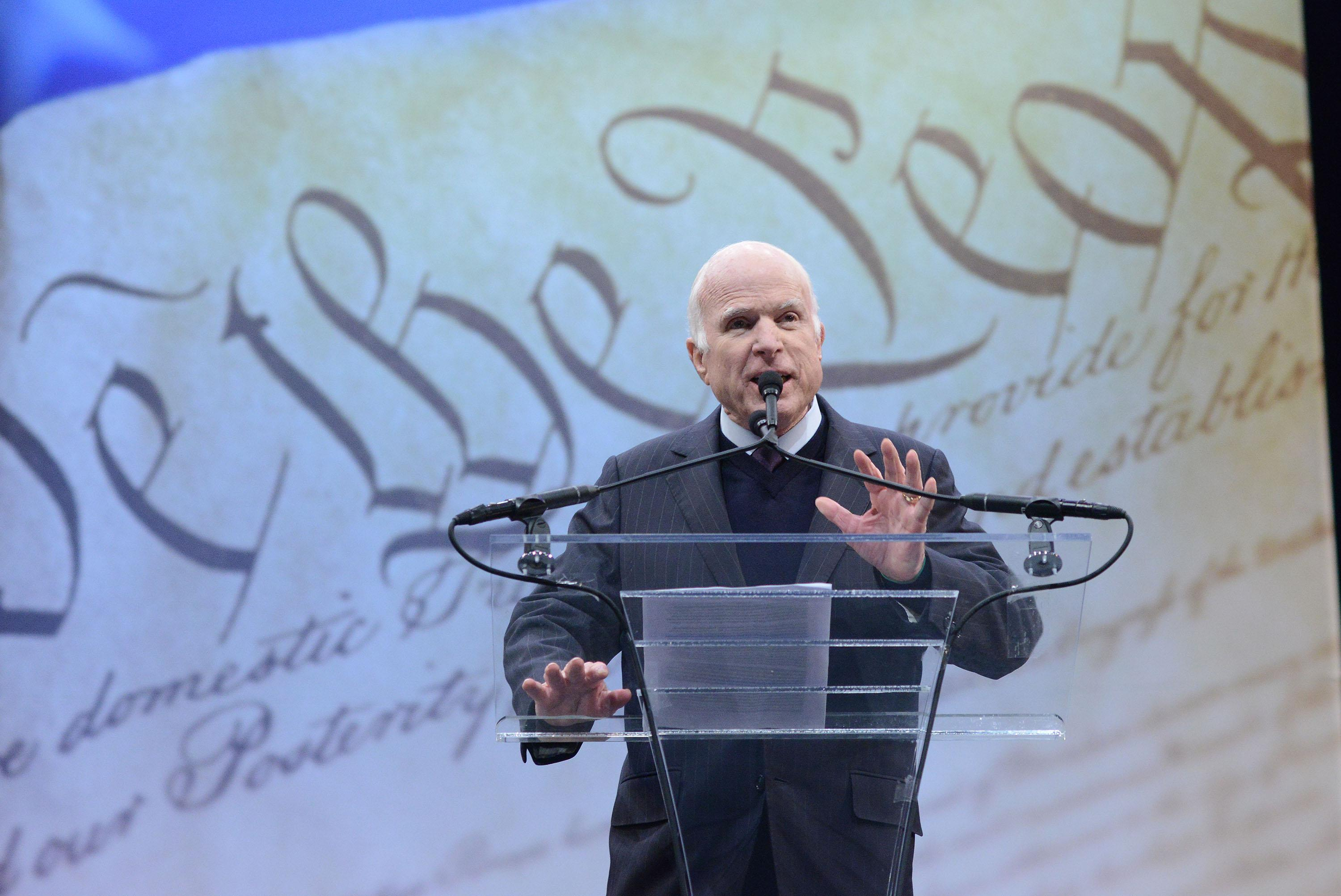 "John McCain stands at a teleprompter on stage in front of an image of the Bill of Rights reading ""We the People."""