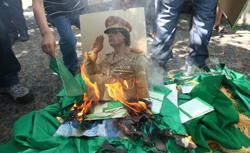 Rebels burn a portrait of Qaddafi. Click image to expand.
