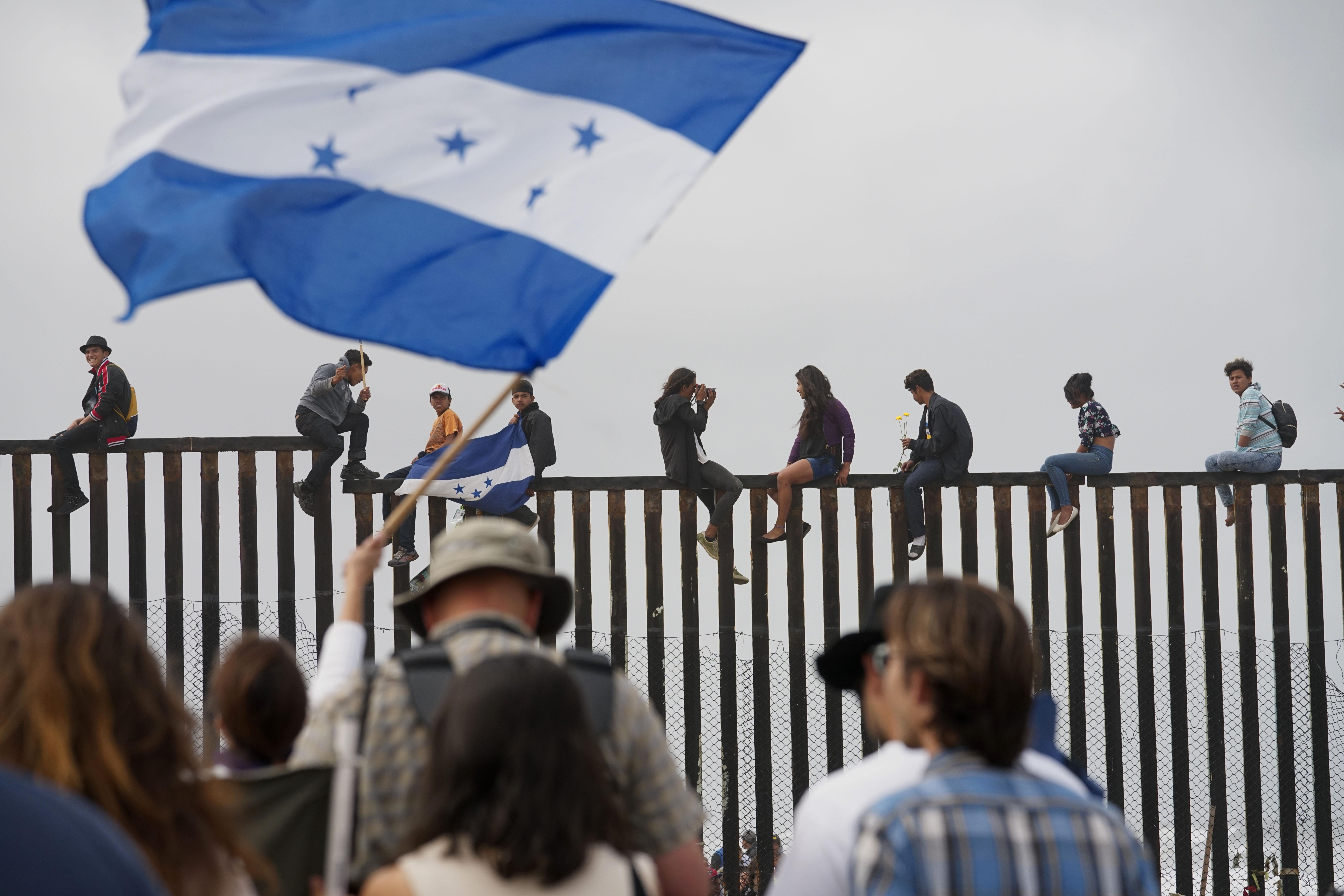 Migrant caravan demonstrators climb the US-Mexico border fence during a rally, on April 29, 2018, in San Ysidro, California.