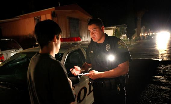 Police Officer Angel Ramirez questions a juvenile victim of an assault in 2010.