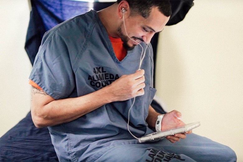 An inmate sits on a cot, smiling as he uses a GTL tablet with earbuds.