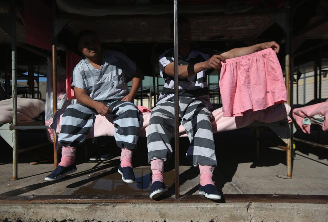 Phoenix, Ariz Immigrant inmates show off a pair of pink underwear while sitting on a bunk in the Maricopa County Tent City jail on March 11, 2013 in Phoenix, Arizona. The striped uniforms and pink undergarments are standard issue at the facility. The tent jail, run by Maricopa County Sheriff Joe Arpaio, houses undocumented immigrants who are serving up to one year after being convicted of crime in the county. Although many of immigrants have lived in the U.S for years, often with families, most will be deported to Mexico after serving their sentences.