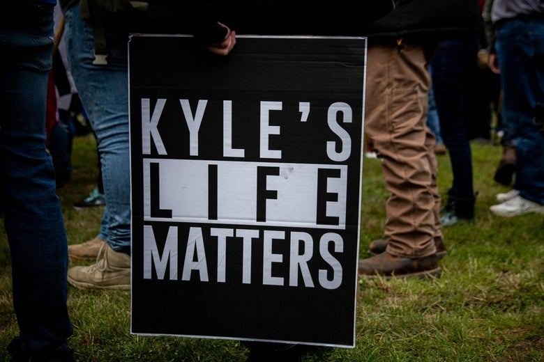 "A person in a crowd holds a sign that reads ""Kyle's Life Matters"""
