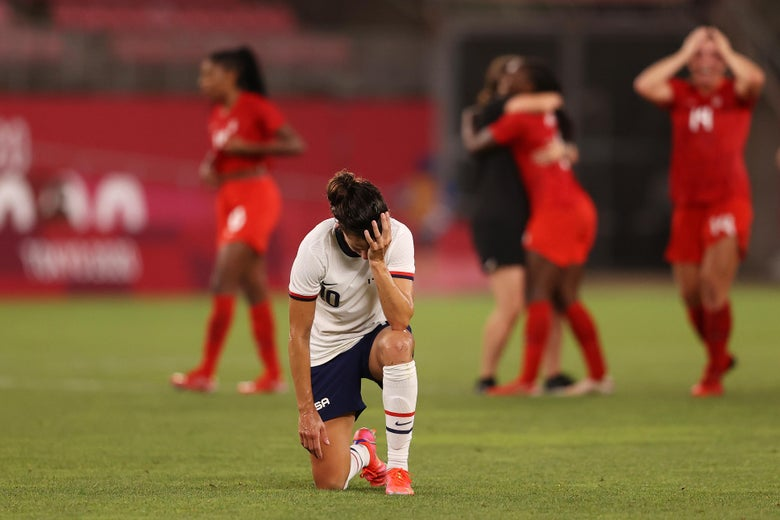Lloyd on one knee with her head in her hand, looking dejected, as Canadian players celebrate behind her.