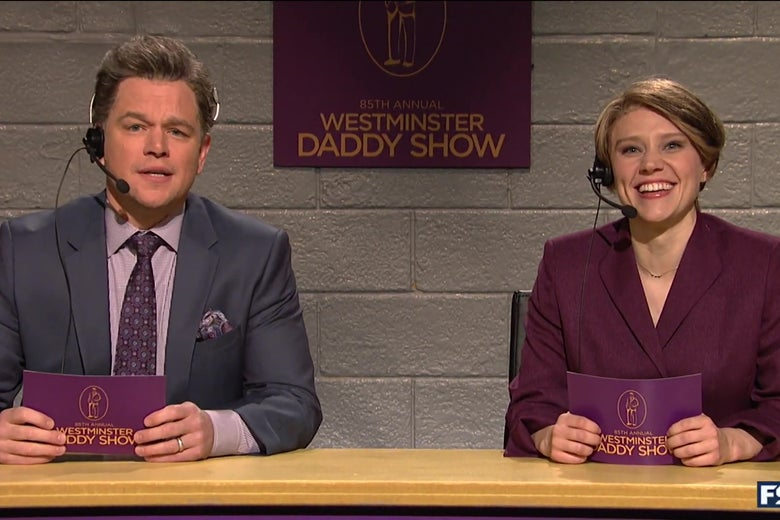 Matt Damon and Kate McKinnon sit at the announcer's podium for the Westminster Daddy Show.