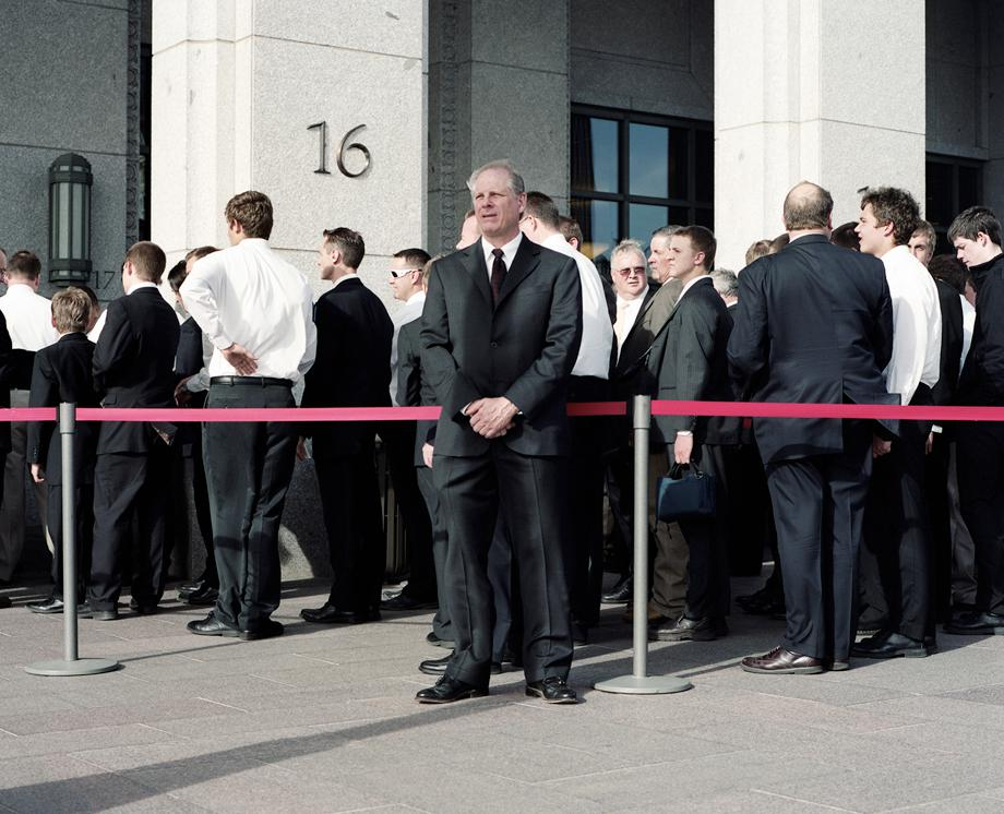 "A Security Guard stands watch as men line up for the priesthood session at the LDS Conference Center during LDS General Conference in April 2012. Twice a year, the Mormon Church holds a ""General Conference"" where over 100,000 Mormons descend on Salt Lake City to hear teaching from leaders in the church and also to learn doctrine from their church president who they believe is a living prophet."