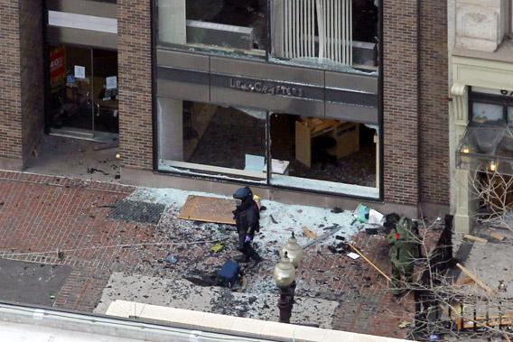 A man in a bomb-disposal suit investigates the site of an explosion that occurred on Boylston Street during the 117th Boston Marathon, April 15, 2013.