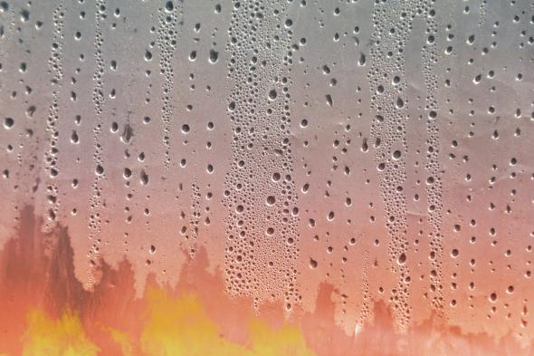 Fire as seen through a window covered in humidity-based condensation
