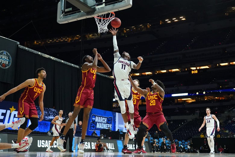 Joel Ayayi in midair with several Trojans players around him