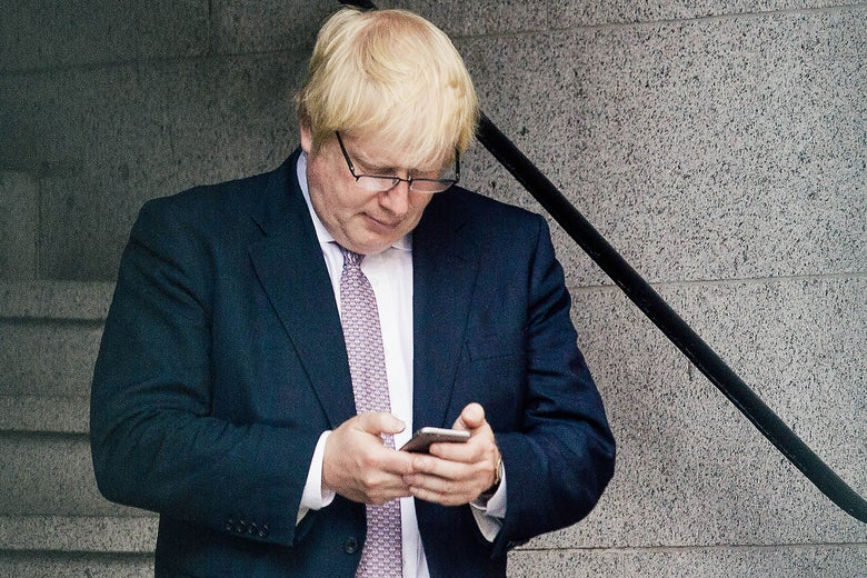 Boris Johnson looks down at a smartphone with his glasses on and a pensive expression.
