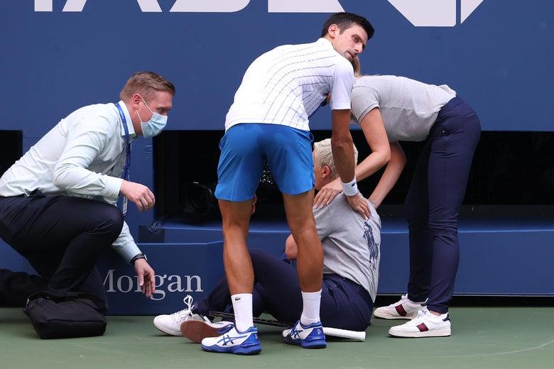 Novak Djokovic tends to a line judge who he hit with a ball.