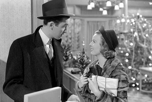 James Stewart wearing a trench coat and a top hat talks to Margaret Sullvan, who is wearing a fur coat and a hat.