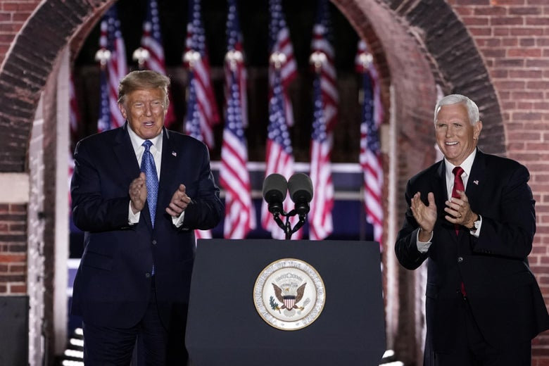 Trump and Pence clap on stage behind of a podium while standing in front of a line of American flags.