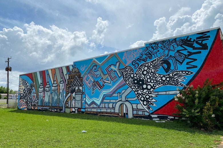 """A mulitcolored mural on a building wall says """"Ensley alive"""" and features flying birds."""