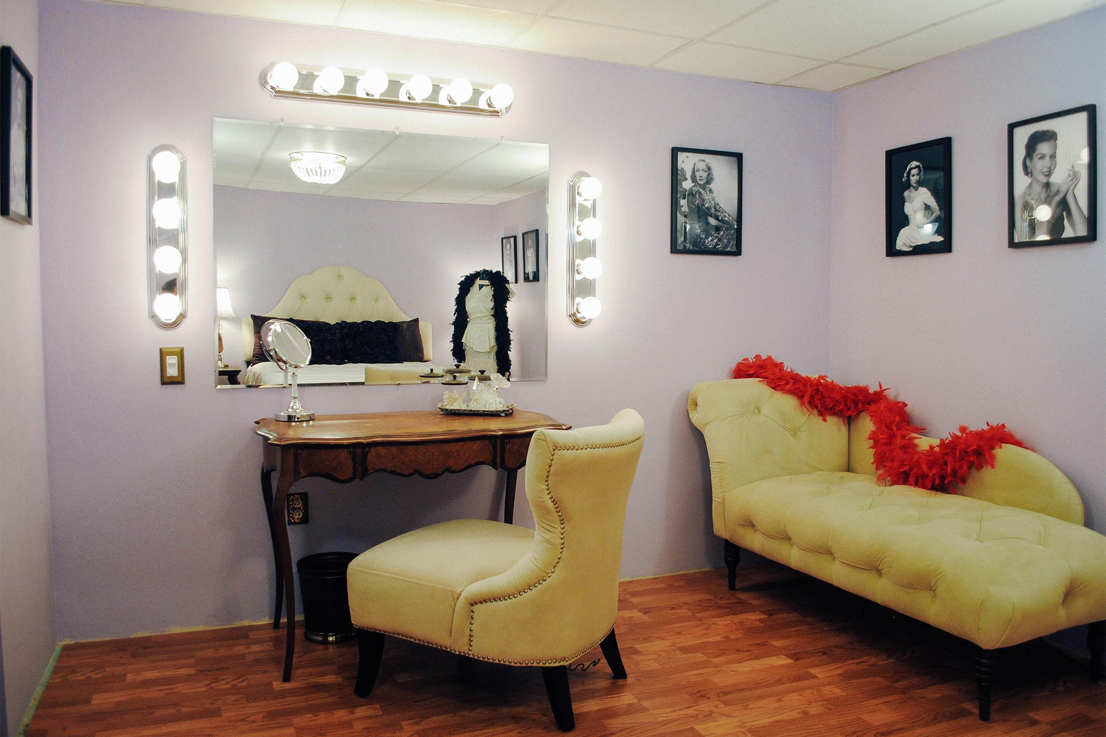 A lavender room with a vanity surrounded by globe lights, and a chaise draped in a red feather boa.