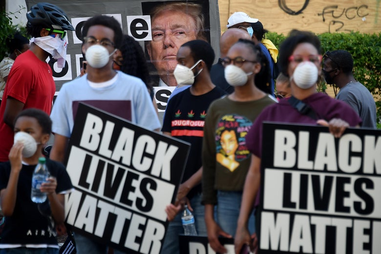 Protesters wearing protective masks for COVID holding up signs protesting police violence and racism.