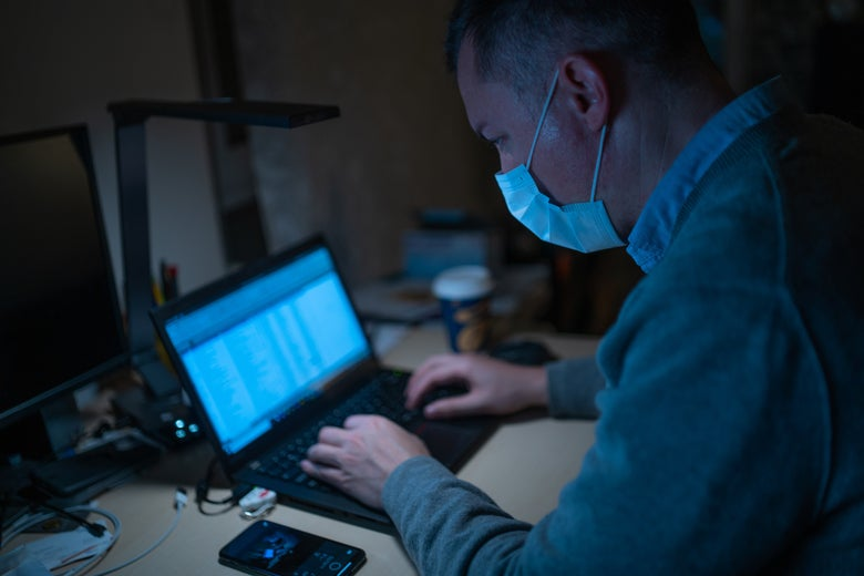 A man wearing a surgical mask types on a laptop at a desk.