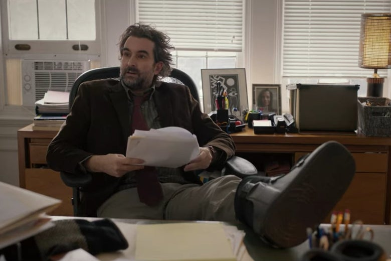 Bill sits on a chair in his office with one leg, injured, up on his desk.