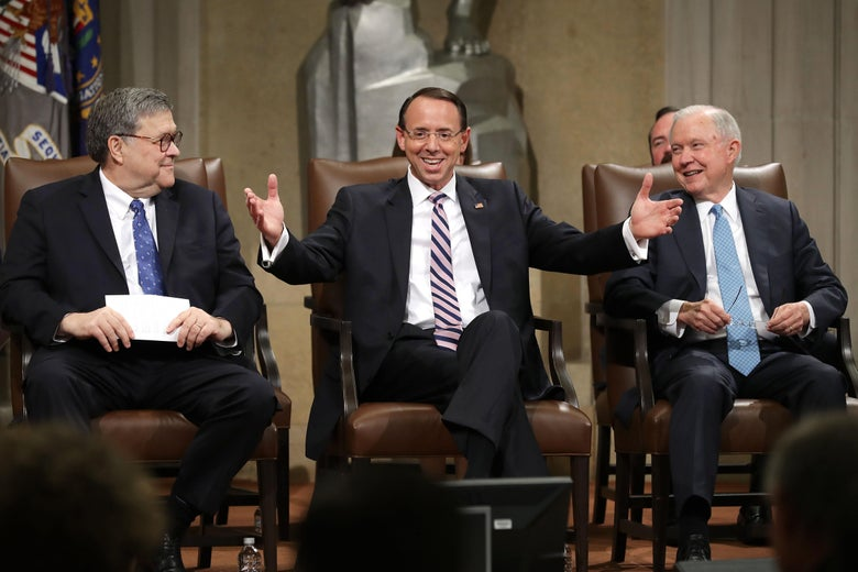 Rod Rosenstein smiles and raises his arms to a crowd as he sits onstage between Bill Barr and Jeff Sessions, both also smiling.