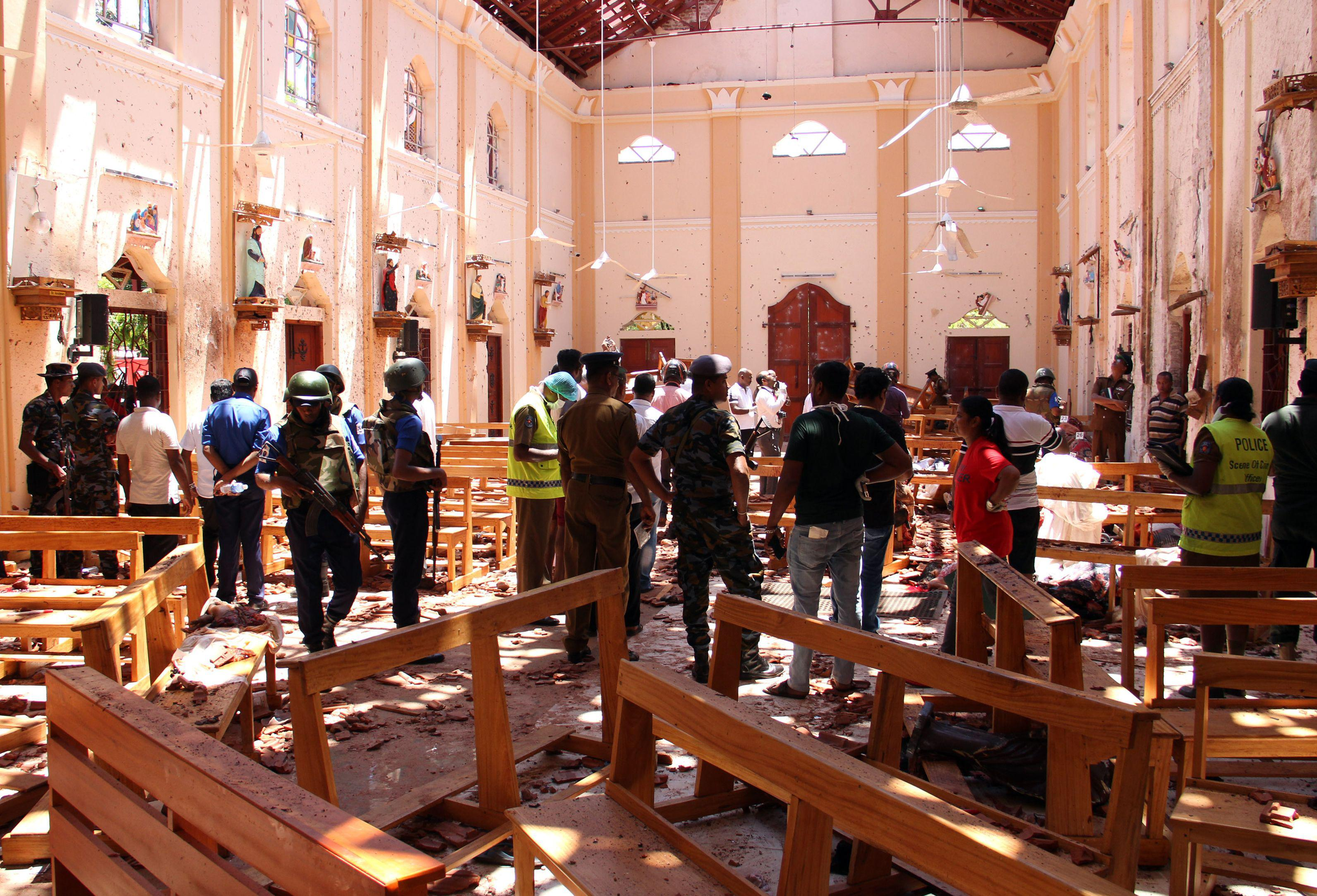 Sri Lankan security personnel walk through debris following an explosion in St Sebastian's Church in Negombo, north of the capital Colombo, on April 21, 2019.