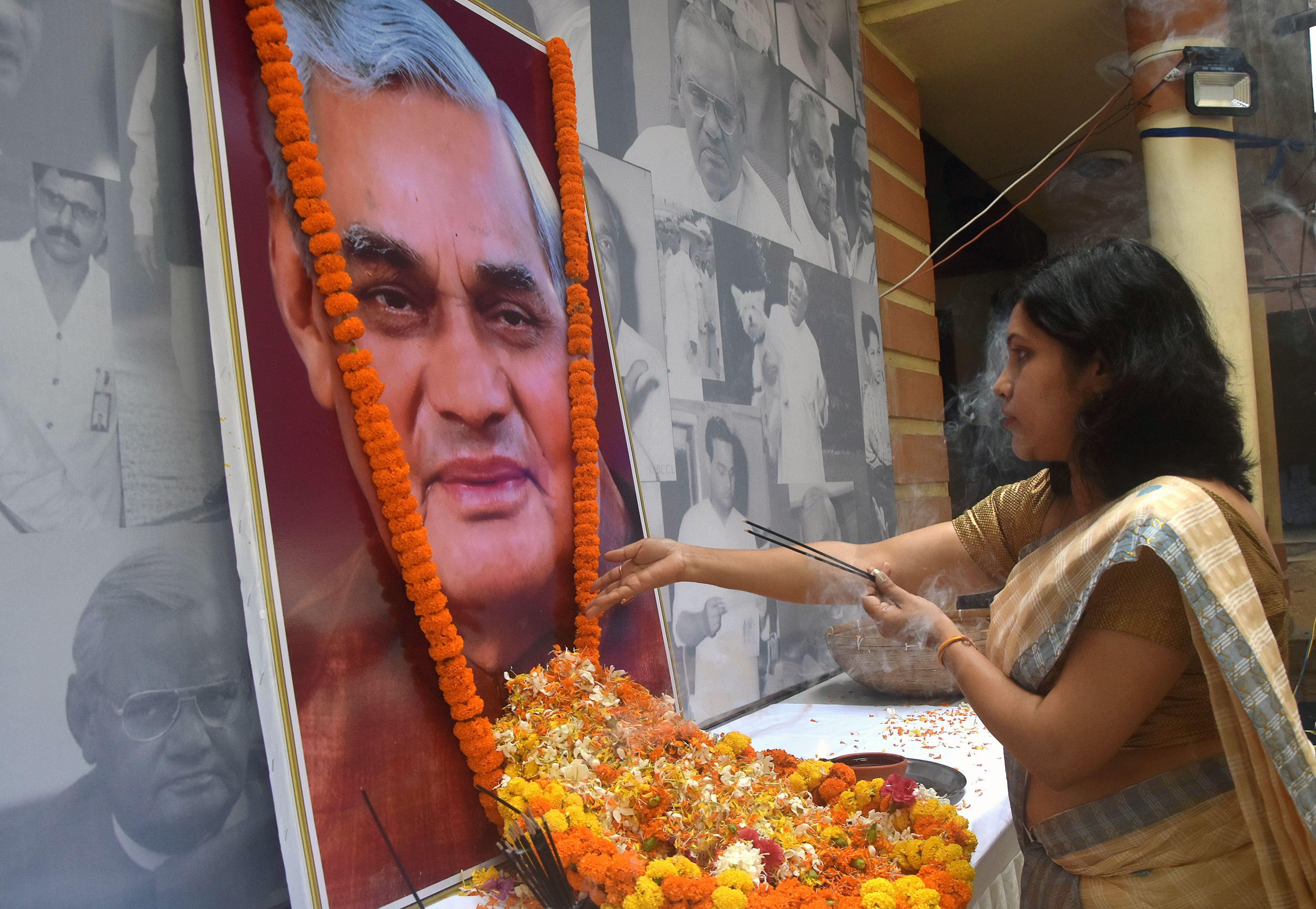 An Indian Bharatiya Janata Party worker pays tribute at a portrait of former Indian Prime Minister Atal Bihari Vajpayee in the state of Guwahati on Friday.
