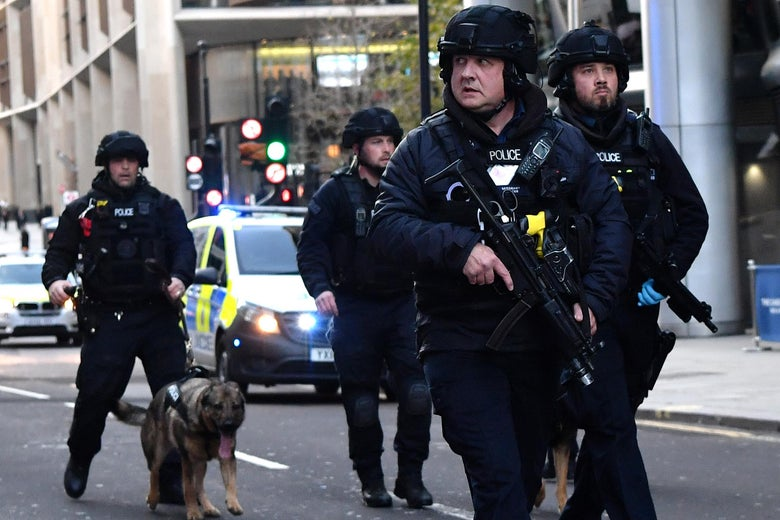 Armed police with dogs patrol along Cannon Street in central London, on November 29, 2019 after reports of shots being fired on London Bridge.