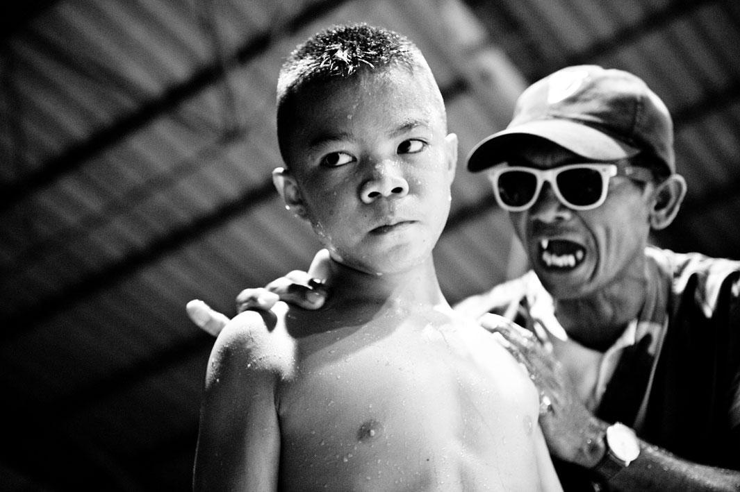 The coach shouts at a boy during the break of the fight.Muay Thai (Thai Boxing) is one of the toughest martial arts in the world. A minimum age for the fighters does not exist. For many poor people it secures their livelihood. For a pittance, they reach their mental and physical limits two or three times a month with boxing matches.