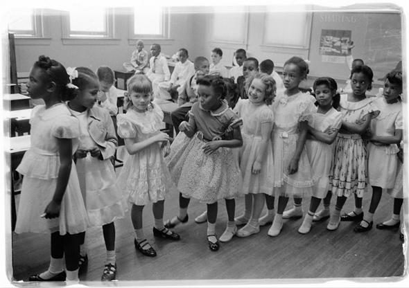 A line of African American and white school girls standing in a classroom while boys sit behind them, May 1955, Barnard School, Washington, D.C.