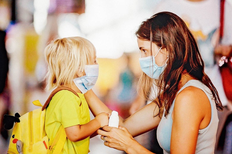 Mom face to face with her child, both wearing surgical masks