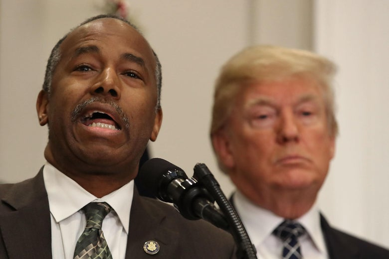 HUD Secretary Ben Carson, with Donald Trump in the background.
