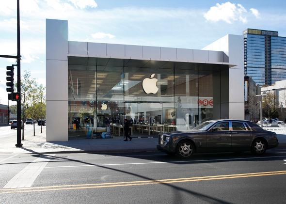 A car drives by an Apple Store in Chicago, Illinois, in 2010. Apple is now rumored to be building a car of its own.
