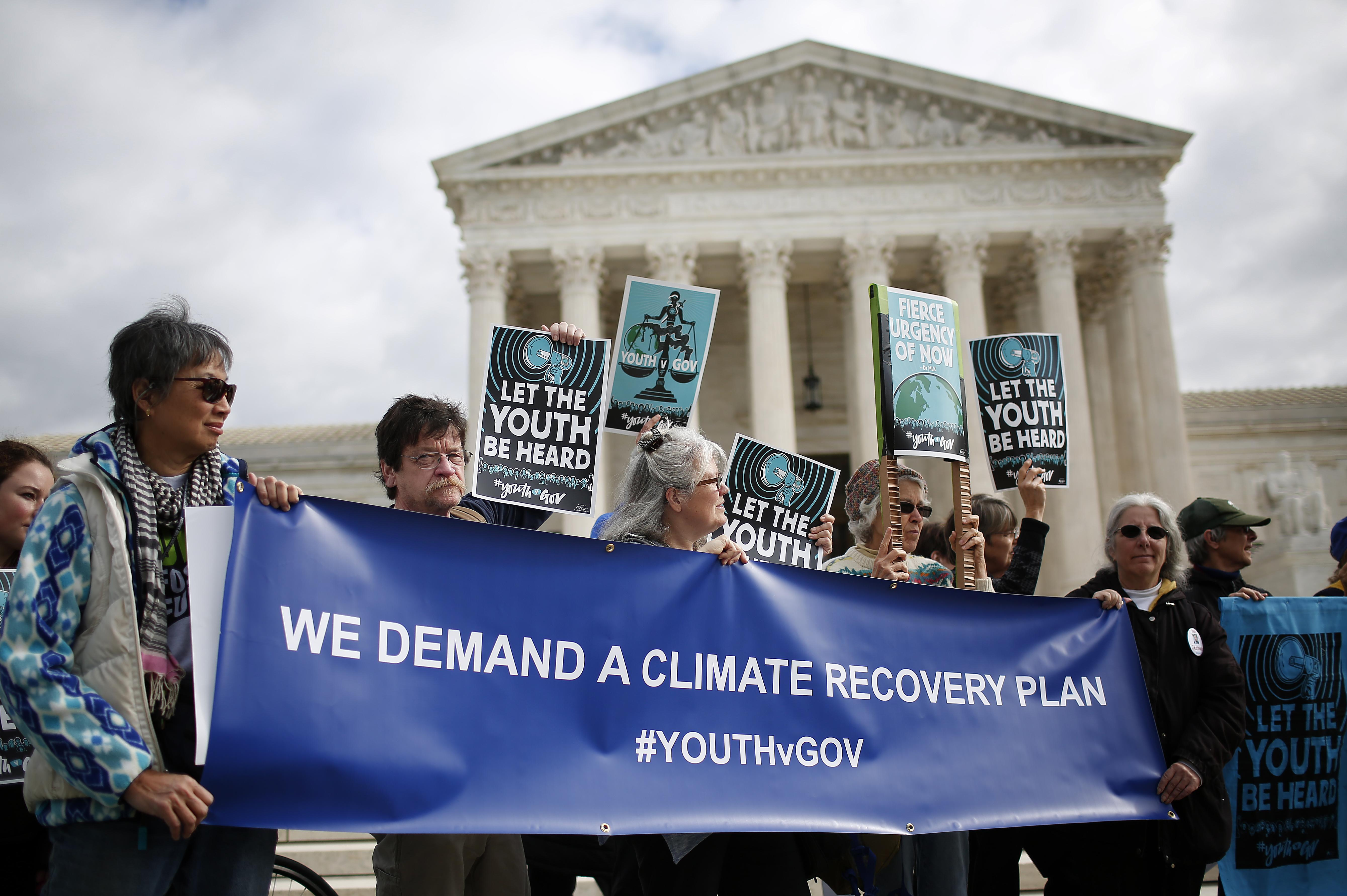 Protesters concerned about climate change attend a rally outside the Supreme Court.