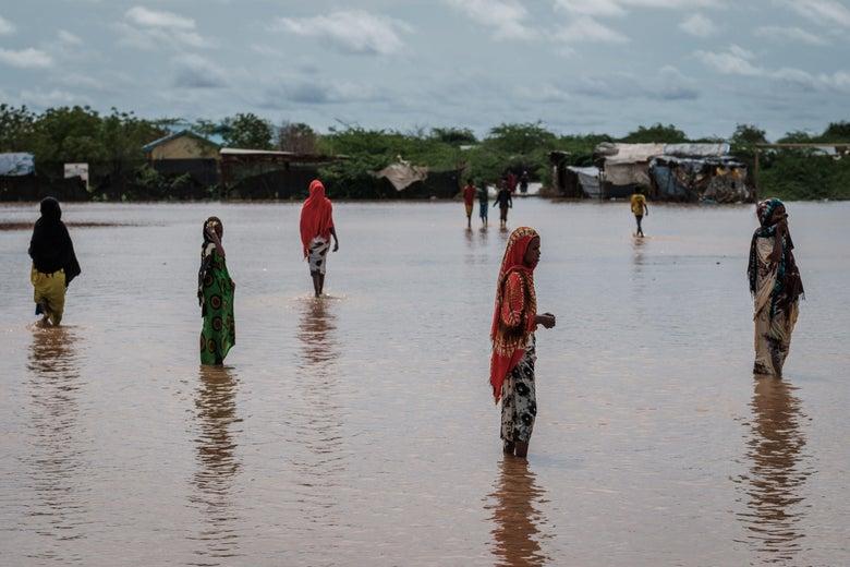 Women walking in ankle deep water outside a refugee camp.