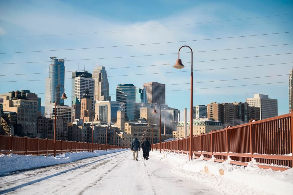 Two people walk on a snow-covered bridge against the backdrop of the Minneapolis skyline.