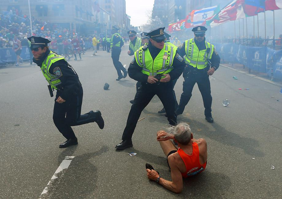 Police officers with their guns drawn hear the second explosion down the street. The first explosion knocked down a runner at the finish line of the 117th Boston Marathon.