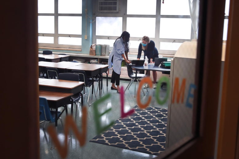 Two teachers in an empty classroom, seen through a window that has a colorful welcome sign on it