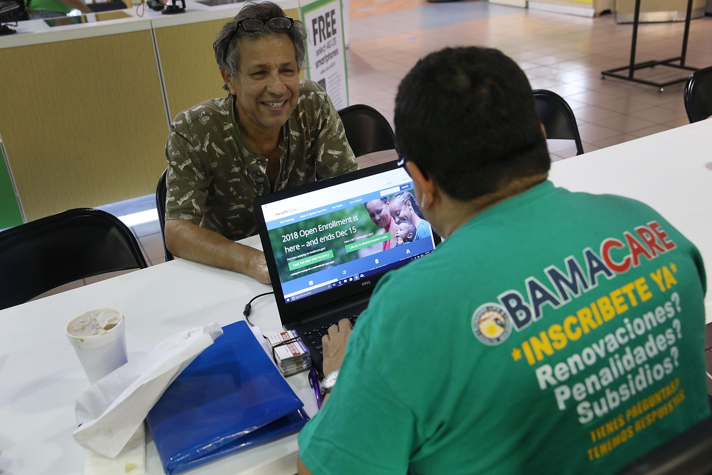 An insurance agent helps someone shop for insurance under the Affordable Care Act at a table in a mall.