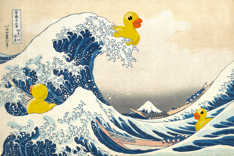 A rubber duckie riding a wave.