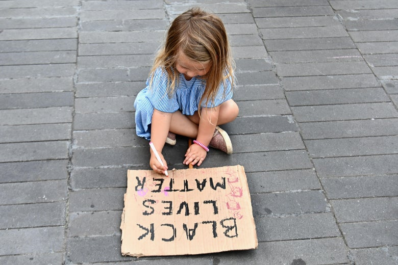 A child paints a sign as families participate in a children's march in solidarity with the Black Lives Matter movement and national protests against police brutality on June 9, 2020 in the Brooklyn Borough of New York City. - George Floyd will be laid to rest Tuesday in his Houston hometown, the culmination of a long farewell to the 46-year-old African American whose death in custody ignited global protests against police brutality and racism.Thousands of well-wishers filed past Floyd's coffin in a public viewing a day earlier, as a court set bail at $1 million for the white officer charged with his murder last month in Minneapolis. (Photo by Angela Weiss / AFP) (Photo by ANGELA WEISS/AFP via Getty Images)