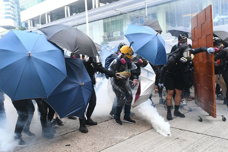 Protesters react after Hong Kong police fire tear gas on a street.
