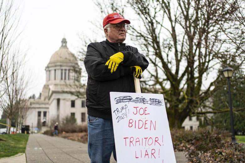 "A lone pro-Trump protestor holds a sign reading, ""Joe Biden Traitor! Liar!"""