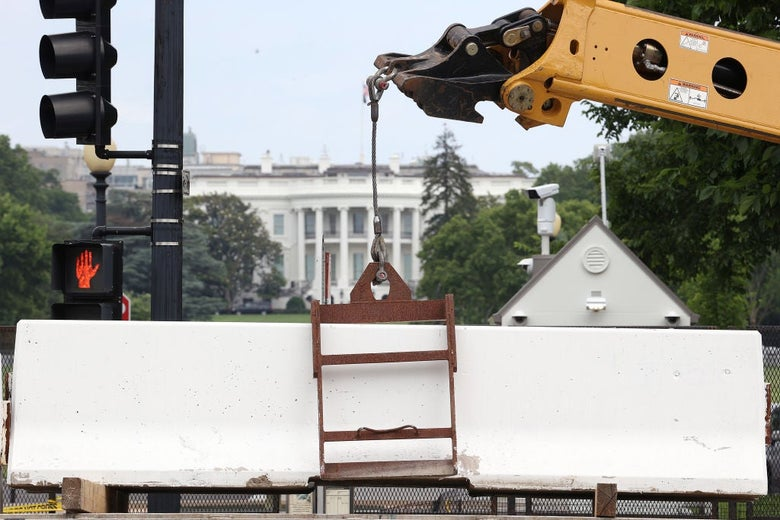 A crane lowers a heavy white barrier into place on a street facing the White House.