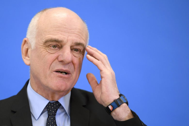 David Nabarro touches his hand to his head